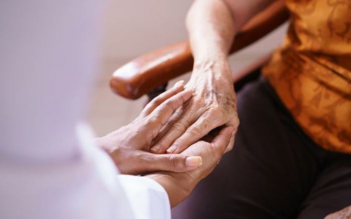Old people in geriatric hospice: Black doctor visiting an aged patient, holding hands of a senior woman. Concept of comfort and compassion