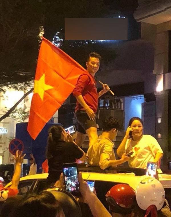 Đàm Vĩnh Hưng mặc quần short, cầm cờ đỏ sao vàng xuống đường đi bão.